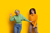 Two beautiful curly haired caucasian women dancing on a yellow background while listening to music from headphones