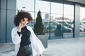Caucasian curly haired caucasian businesswoman talking on phone with an entrepreneur outside in a white shirt