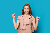 Cheerful caucasian woman with red hair and pretty freckles is gesturing the power sign covered with a sweater on a blue background