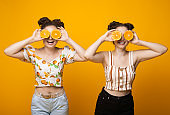 Front view photo of two caucasian twins covering her eye with oranges and smile on a yellow studio wall