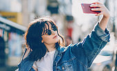 Close up portrait of a cheerful lady making a selfie while looking through her sunglasses and wearing blue jacket
