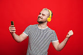Caucasian man with blonde hair dancing on a red background while listening to music through headphones