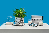 White table with candles on it and in a glass candlestick, green plant in pot, glasses, iron triangle, home decor element. Blue background. Close up