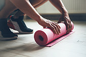 Caucasian man finishing doing exercises is gathering his yoga carpet from the floor