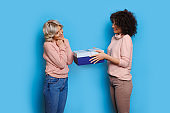 Brunette woman with curly hair giving a gift to her blonde sister who is gesturing happiness on a blue studio wall