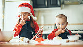 Caucasian brother and sister preparing food for the christmas holidays wearing santa clothes in the kitchen