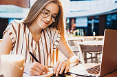 Ginger caucasian student with freckles making some notes while working with a computer in a restaurant