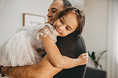 Charming caucasian girl dressed in a white dress looking back while her father is holding and embracing her