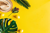 Summer composition. Tropical leaves, hat, fruits on yellow background. Summer concept. Flat lay, top view, copy space