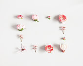 Flowers composition. Frame made of pink flowers on pastel gray background. Valentines day, mothers day, womens day concept. Flat lay, top view, copy space