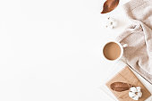 Autumn or winter composition. Cup of coffee, gift, dried autumn leaves, beige sweater on white background. Flat lay, top view
