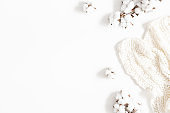 Blanket, cotton flowers on white background. Flat lay, top view, copy space