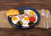 English breakfast with fried eggs, bacon, tomato, toasts and broccoli in the plate that is on burlap, on wooden background, angle view
