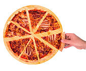 Close-up of male hand taking a slice of BBQ pizza with ham, bbq sauce, bacon and salami from the wooden plate, isolated on white, top view