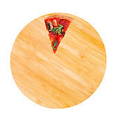 A slice of delicious pizza with salami, arugula, tomatoes, mushrooms and texas spice mix, on a wooden round platter, isolated on white, top view