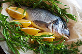 Raw dorado with lemon and aromatic herbs prepared for grilling, close-up