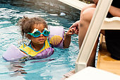 Mixed-race toddler and mother having fun in the pool.