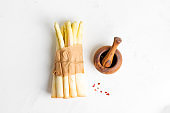 Bunch of freshly picked raw organic white asparagus and wooden mortar with paper on a light grey stone background.