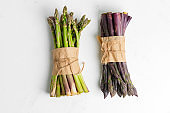 Fresh natural organic two bundles of green and purple asparagus vegetables on a stone background.
