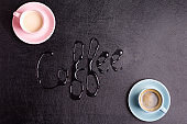 Two cups with fresh aromatic morning drink on a decorative black artificial eco leather background and water text Coffee. Top view.