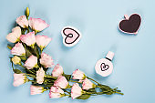 Blooming pink eustoma with perfume heart and wooden chalk board, flat lay. Floral decorative corners on blue background.