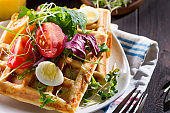 Close up view of freshly cooked healthy breakfast with homemade waffles, tomatoes and cut egg on a plate on a wooden background.