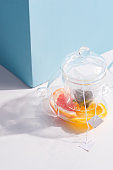 Summer homemade cold fruit tea drink in a glass transparent teapot on a white table with shadow against pastel blue wall.