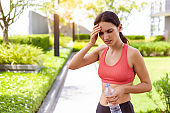 Sport woman thirsty dehydrated in hot weather Dehydration, overheating, thirst, heat stroke, health care concept with girl in strong sunny day. She get dizzy, fainting after running outdoors in summer