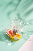 Glass teapot with ingredients for preparation cold summer homemade fruit tea on a duotone background with shadows from leaves.