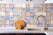 Shiny stainless steel faucet with chrome water tap, stone sink and wooden bowls with olive olives on a background of colored old tiles. Kitchen interior