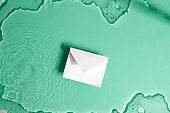 Paper mockup envelope on a water under glass texture.