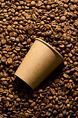 Paper mockup eco friendly cup on a pile of coffee beans.