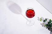 red wine in a wineglass with shadows isolated on stone background