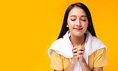 Dedicated Christian young lady praying to God. Woman praying with hands together on yellow background. Attractive girl thank you for god blessing to wishing have a better life. She believe in goodness