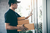 Young asian courier is using the hand of the knock at the door to deliver the goods.