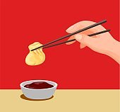 Hand dumpling with chopstick to sauce.traditional chinese food symbol in cartoon illustration vector