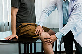 Asian physiotherapists are checking patients' knees.