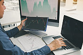 Close up of hand investors are pointing to laptop computer that have investment information stock markets and partners taking notes and analyzing performance data.