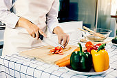 Woman using knife and hands cutting tomato on wooden board in kitchen room.
