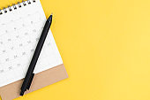 Black pen on desktop calendar in flat lay or top view on yellow background with copy space using as writing plan, circle on important day and event or appointment concept
