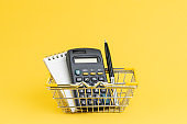 Shopping list, cost and expense to buy things at minimart or supermarket concept, calculator with note paper and pen. in mini shopping basket on yellow background