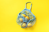 Mesh shopping bag with lemons on yellow paper background. Flat lay, top view. Zero waste, plastic free concept. Healthy clean eating diet and detox. Summer fruits