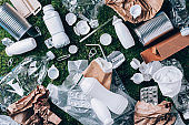 Plastic waste, food packaging, trash collection on green moss background after picnic in forest. Plastic free. Top view. Copy space. Recycling plastic. Environmental pollution, ecology concept.