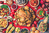 Roasted Christmas chicken with orange slices, cranberries, garlic, festive decoration, candles, tangerine, pomegranate, golden cultery, star glitter sparkles on red background. Top view, copy space. Festive family Christmas dinner.