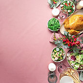 Festive family dinner table. Serving plates, bowls with salads and vegetables dishes, snack, whole roasted chicken, eucalyptus flowers on pink shabby background. Valentine day, Women's Day, mother's day, wedding brunch, festive family lunch