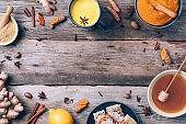 Healthy vegan turmeric latte or golden milk, turmeric root, ginger powder, black pepper over wooden background. Antiviral beverage. Spices for ayurvedic treatment. Alternative medicine concept