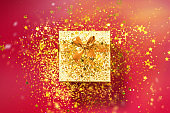 Gift box with sparkling gold glitter on red background. Romantic card. New year, Christmas, Valentine's day concept of greetings. Copy text. Top view, flat lay.
