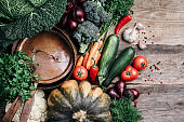 Healthy, clean food cooking and eating concept. Copper pan, colorful autumn vegetables on wooden background. Top view. Copy space. Vegetarian cooking ingredients. Autumn harvest fair.