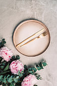 Flower arrangement on table served for festive dinner with copy space for your text, invitation. Greeting card. Top view. Peony, eucalyptus, plates, golden cutlery, wineglasses on marble background
