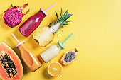 Detox summer drink. Vegan, vegetarian, fructorian diet. Fresh smoothie and juicy fruits - papaya, orange, pineapple, dragon fruit, pitahaya, tamarillo fruit over yellow background. Top view, flat lay, copy space
